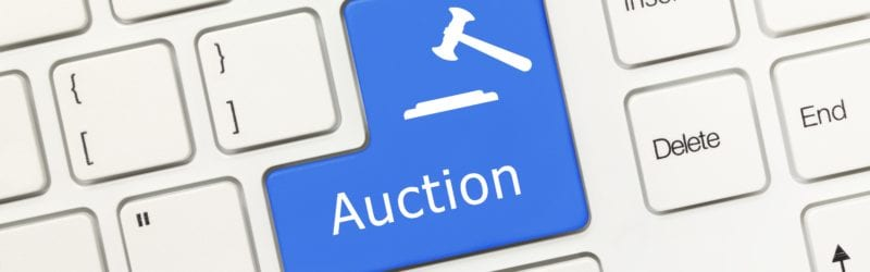 """A white keyboard with a blue """"Auction"""" button replacing the enter button"""